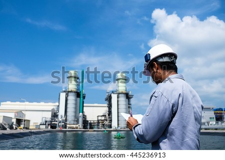 engineer is recording data with power plant background