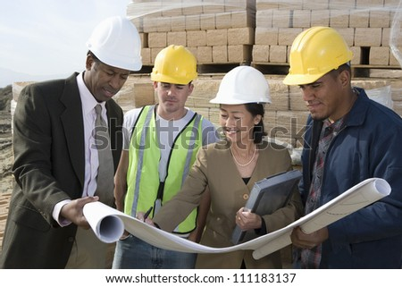 Engineers showing blueprint at construction site