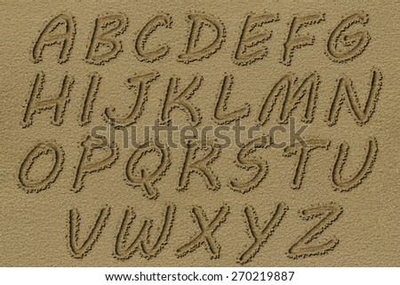English alphabet written on a beach sand.