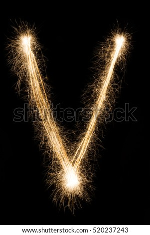 English big Letter V made from burning sparkles on black background. Shiny festive party firework font, latin alphabet text sign.
