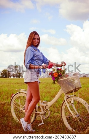 enjoying cycling series: portrait of beautiful brunette young woman having fun with bicycle on green summer outdoors copy space background