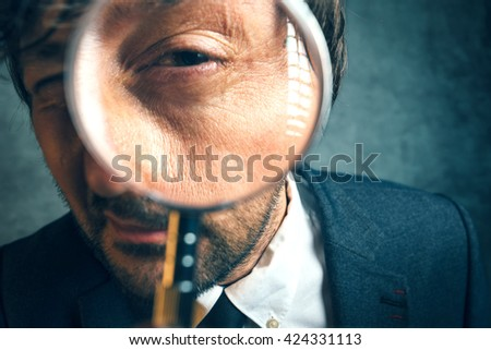 Enlarged eye of tax inspector looking through magnifying glass, inspecting offshore company financial papers, documents and reports.