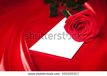 Envelope and red rose over abstract satin background