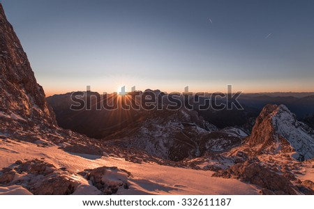 Epic sunset in the winter mountains. Male hiker waiting for the sun to go behind the mountains. Fantastic scenery in Julian Alps.