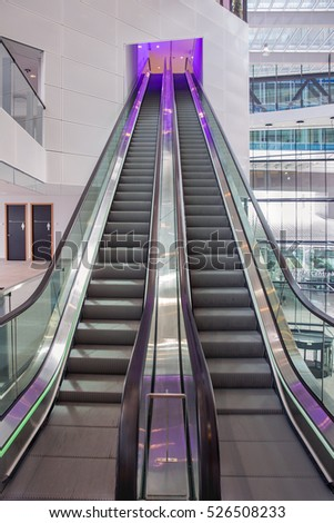 Escalator with purple illumination in a modern office building