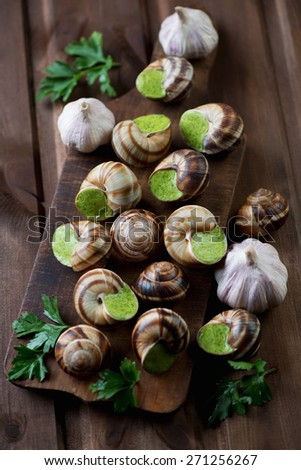 Escargots de Bourgogne on a rustic wooden chopping board