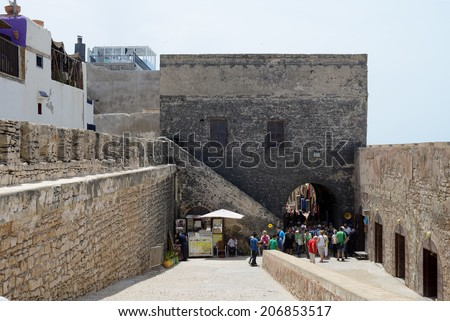 ESSAOUIRA, MOROCCO - MAY 14, 2014: Tourists arriving at historical landmark of fortress by the sea. Essaouira, Morocco. May 14, 2014.