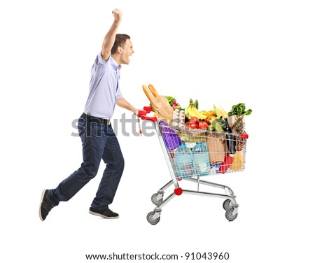 Euphoric man pushing a shopping cart full with food isolated on white background