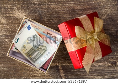 Euro banknotes inside the gift box on the wooden background