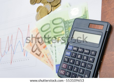Euro currencies with calculator and data analysis of stock market or sales. Business and finance concept image. 50 and 100 Euros bank notes with coins.