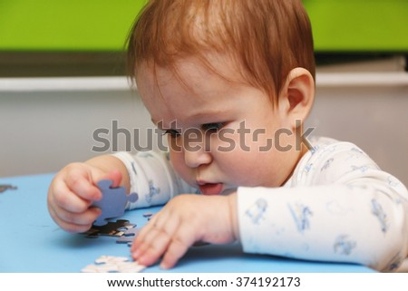 European baby develops older brother puzzle in the children's room on the table