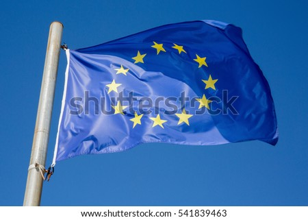 European Union blue flag with yellow stars under blue sky