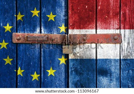 European Union flag with the Holland flag on the background of old locked doors