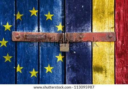 European Union flag with the Romanian flag on the background of old locked doors