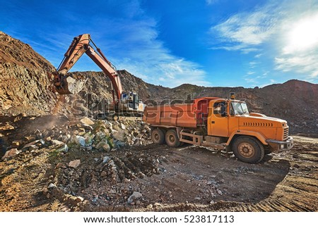 Excavator and truck in a gravel quarry. Minerals and ores. Open pit mining. Rising Sun.