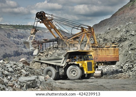 Excavator developing the iron ore on the opencast and loading it to the dump truck