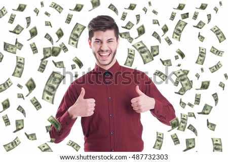 Excited businessman raising thumbs up and standing under money rain
