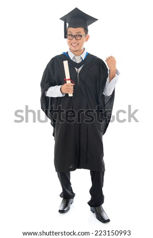 Excited full length Southeast Asian university student in graduation gown, standing isolated on white background.