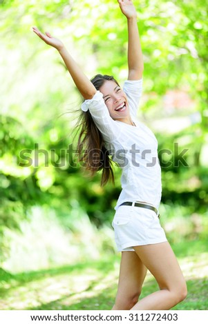 Excited joyful young woman with arms raised in happiness jumping in spring park enjoying summer. Happy mixed race Asian / Caucasian female walking on sunny day wearing white casual clothing