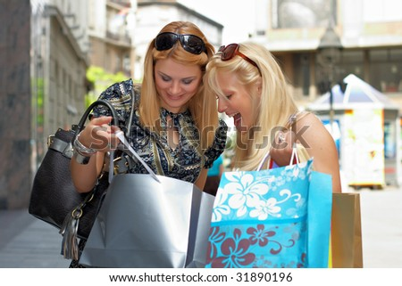 Excited shopping woman looking what her friend purchase in street environment.