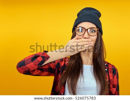 Excited surprised young woman covers hands open mouth over yellow background. Emotional female portrait. Hipster girl.