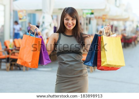 Excited young woman shopping in the city.