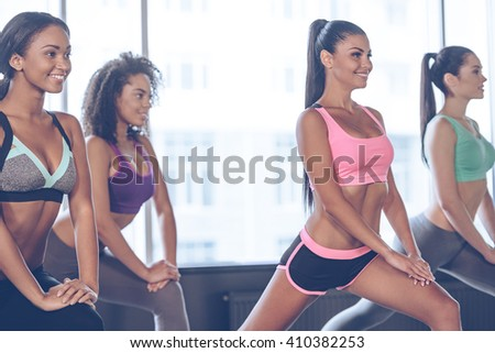 Exercising with pleasure. Close-up of beautiful young women with perfect bodies in sportswear exercising with smile while standing in front of window at gym