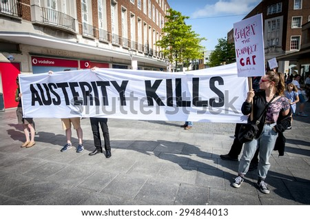 EXETER - JULY 8: The Austerity Kills banner is held up during the Exeter Budget Day Action #AusterityKills in Exeter City Centre on july 8th, 2015 in Bedford Square, Exeter, UK