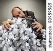 Exhausted depressive businessman laying on big heap of crumpled papers - stock photo