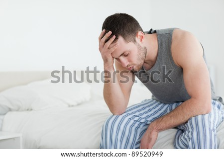 Exhausted man sitting on his bed with his eyes closed