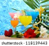 exotic cocktails and flowers on table on blue sea background - stock photo