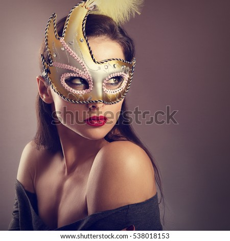 Expressive female model posing in carnival mask with red lipstick and looking vamp on empty copy space background. Closeup portrait. Toned art.