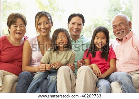Extended Family Relaxing On Sofa At Home Together