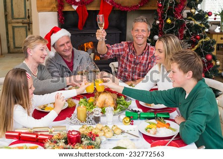 Extended Family Toasting At Christmas Dinner Home In The Living Room
