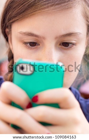 Extreme close-up of girl texting on her handheld mobile cell phone with focus on eyes.