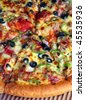 """Extreme close-up view of a section of a pizza """"supreme"""" with all the trimmings - stock photo"""