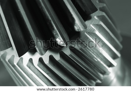 extreme close-ups of two gears connecting in a metallic greenish cast