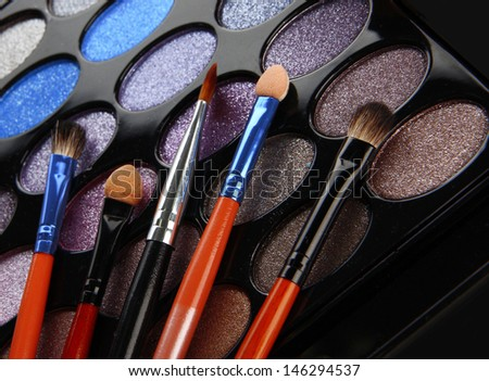 eye shadows and brushes on white background