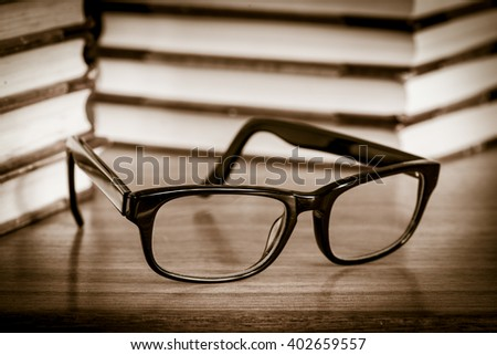 Eyeglasses lying on table with stacks of book in the background. Concept of education, reading literature or studying hard.