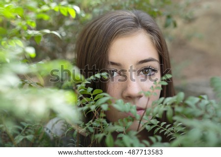 Face of a girl among branches of a tree with green leaves