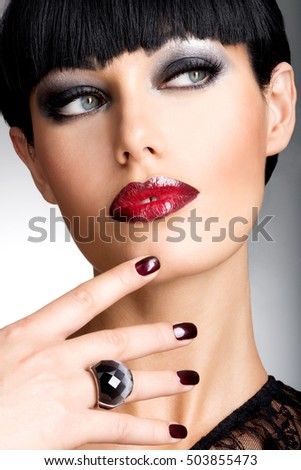 Face of a woman with beautiful dark nails and sexy red lips. Fashion model with black shot hairs at studio