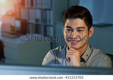 Face of cheerful programmer working on computer in dark office