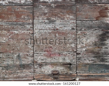 Fading red and grey planks with dark spots and metal latch on bottom.