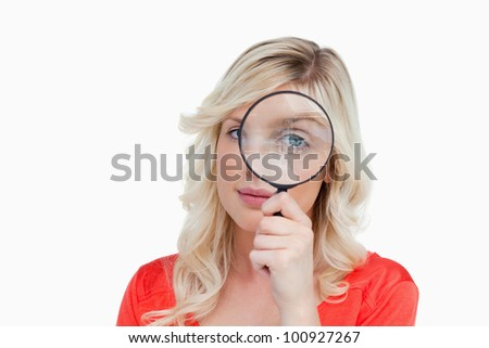 Fair-haired woman looking through a magnifying glass against a white background