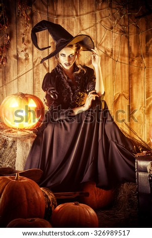 Fairy witch in black dress in a wooden barn with pumpkins. Halloween.