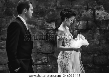 Fairytale romantic beautiful bride with veil walking with handsome groom old wall background