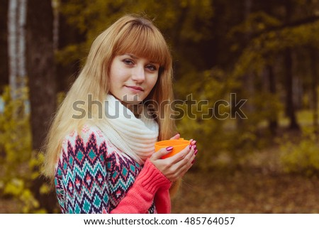Fall concept - autumn woman drinking coffee in park
