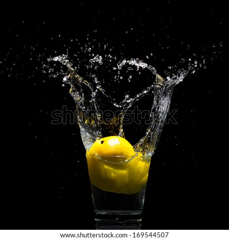 Falling lemon to glass with water