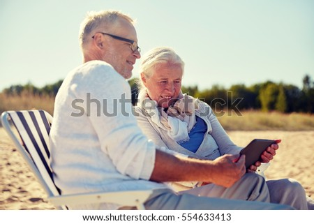 family, age, travel, tourism and people concept - happy senior couple with tablet pc computer resting in folding chairs on summer beach