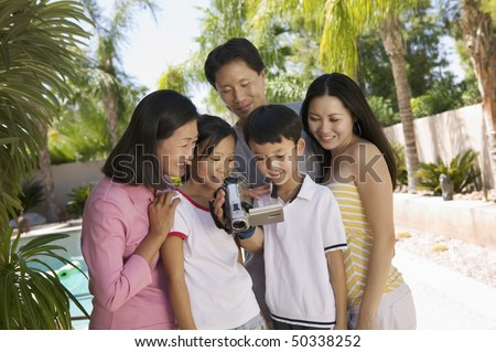 Family by pool in backyard Looking at Video Camera Screen, front view